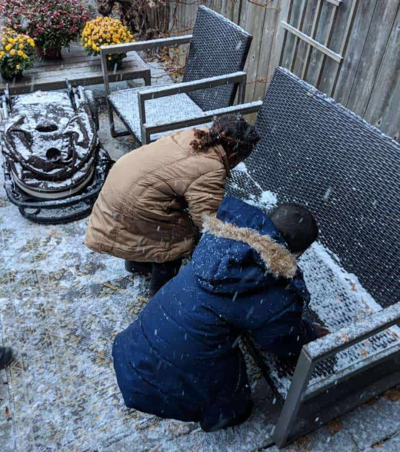 Eritrean children see snow for the first time and try to scoop up snow off bench