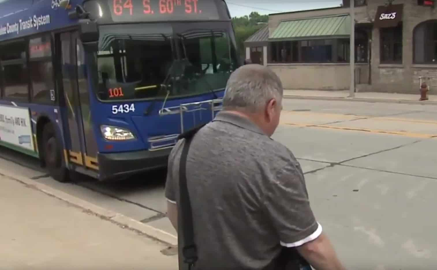 bus driver helps elderly blind man cross road